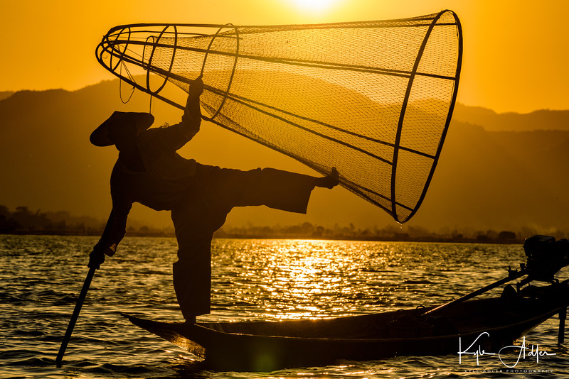 An Intha fisherman with the tools of his trade as the sun sets on Inle Lake.