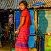 A teen resident of the bamboo village does chores while her young sisters play inside their home.