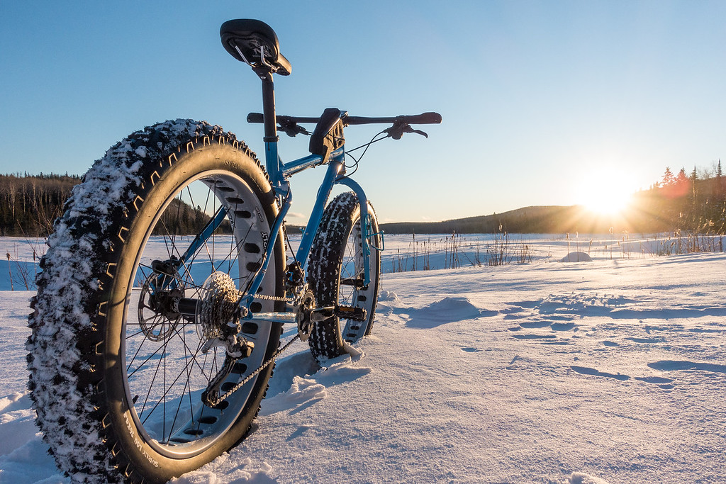 "BIKING 08509<br /> <br /> ""Fat Bike Sunset""<br /> <br /> February 14, 2016 - Since I shared a shadow picture of me and my bike yesterday, I figured I better show a picture of the actual bike too!  So, here is my Surly ""Ice Cream Truck"", admiring the setting sun on a clear, cold day.  For those that don't know, fat bikes allow you to ride on packed trails in the winter.  They have tires that are at least twice as wide as a typical mountain bike tire, and you run very low pressures in them (5 to 10 psi compared to at least  30 to 35 psi in a mountain bike and probably twice that in a road bike tire).  The large tire footprint and the low pressure gives you tremendous flotation for a bike, allowing you to ride on snow as long as you have a reasonably firm trail to ride on."