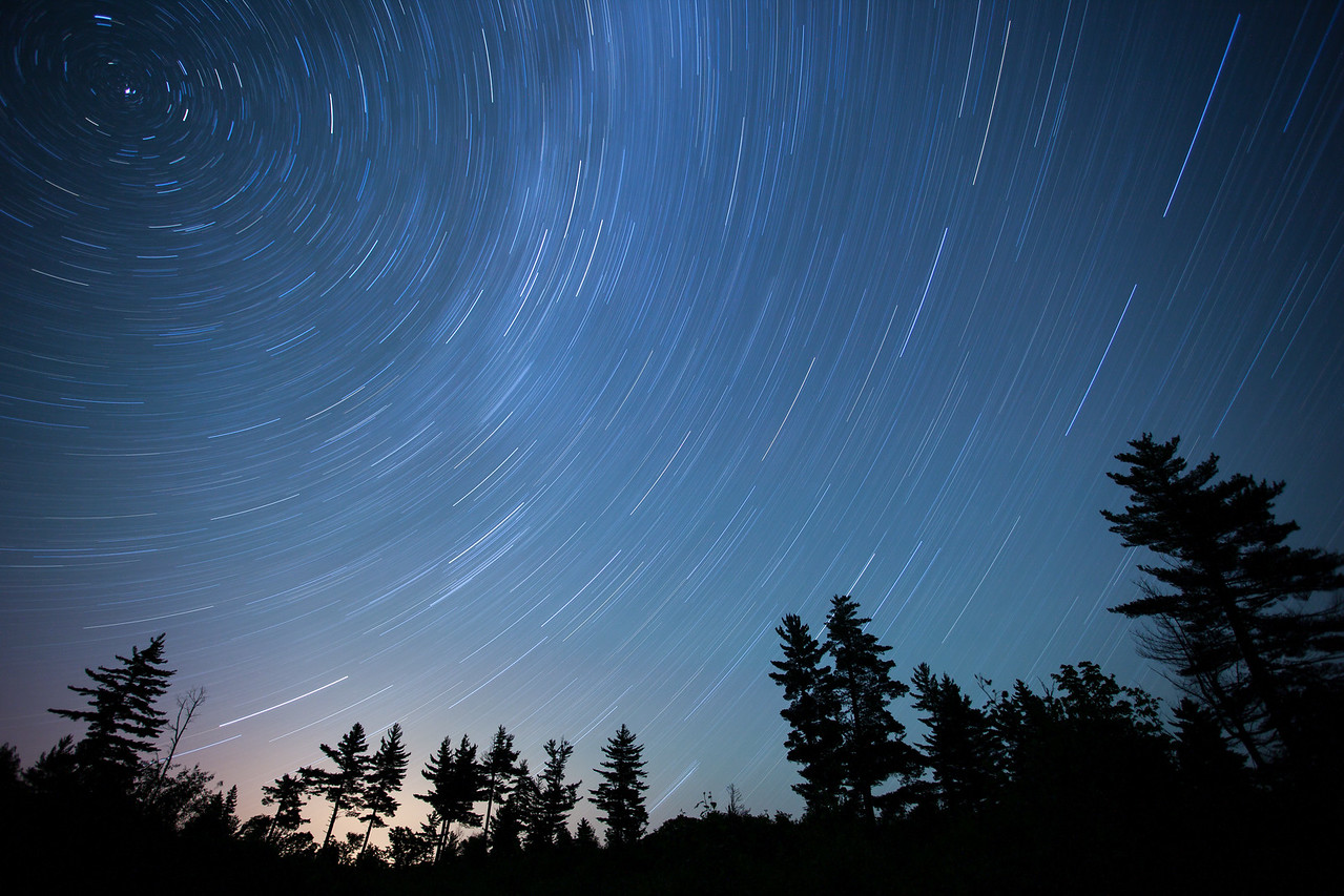 "STAR TRAILS 8744<br /> <br /> ""Passing Time with the Pines""<br /> <br /> 49 minute exposure made at 12:43 AM on the morning of July 30, 2014."