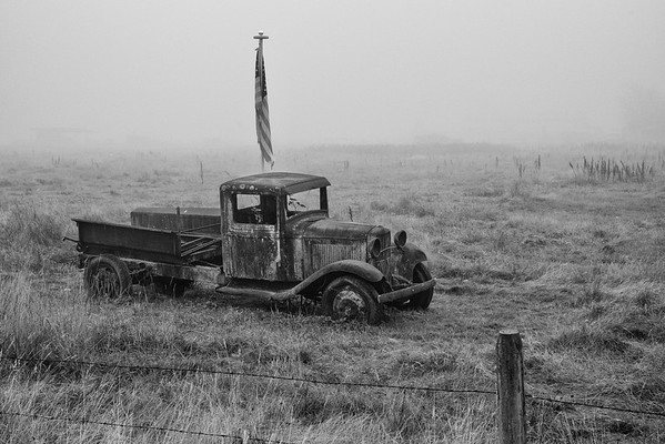 A lone and rusting truck is now the bearer of the stars and stripes. There is no wind to unfurl the flag. Have hope that the winds of change are coming and we will be renewed.
