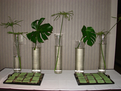 sign-in table filled with different height cylinder vases with monstera leaves and papyrus leaves