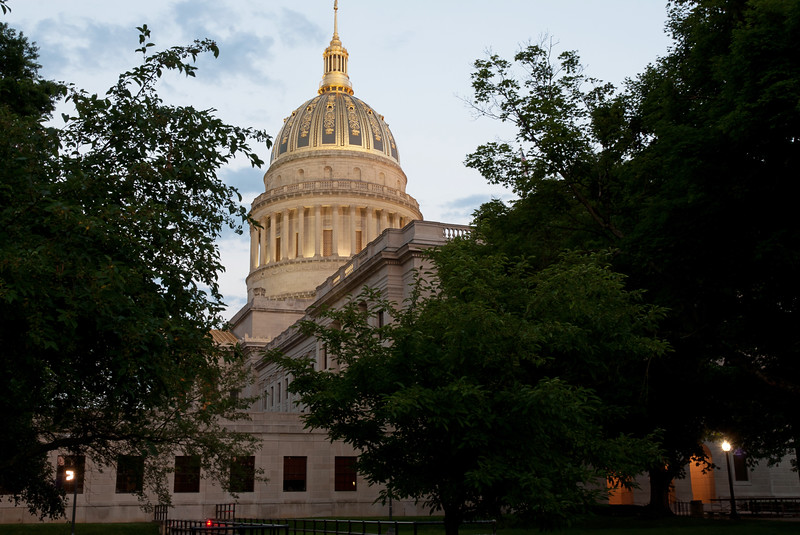 The gold domed State Capitol building in Charleston, WV, at dusk.