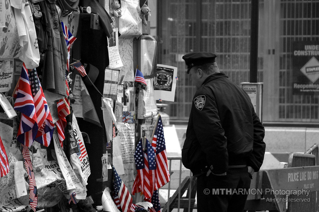 New York City Police Officer at a memorial wall in front of St. Paul's Episcopal Church, Ground Zero.  (New York, NY)