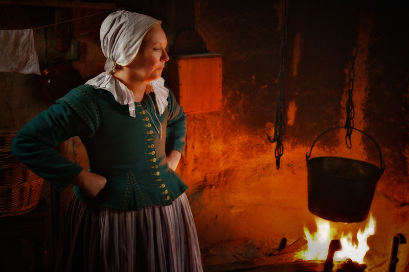 Life in Plymouth Colony: Costumed Female Pilgrim Interpreter Standing in Front of Hearth, 1627 English Village, Plimoth Plantation, Plymouth, Massachusetts