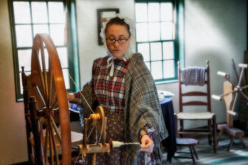 Colonial Era Daily Life: Costumed Female Interpreter at the Spinning Wheel. Fenno Textile Exhibit, Fenno House, Old Sturbridge Village, Worcester County, Massachusetts