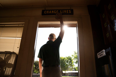 Service Academy Coordinator Jonathan Kaup taps the Change Lives sign on his way out of the Ranger Office on June 6, 2021.