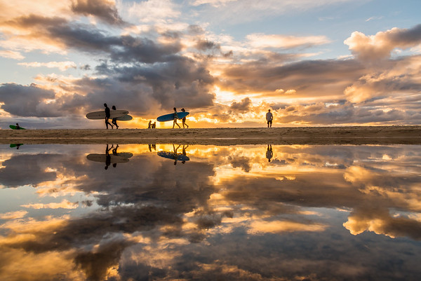 reflection of beach goers and surfers at Byron Bay Beach.