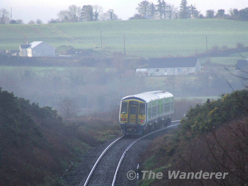"In murky weather 2707 + 2708 descend ""The Boar"" heading downhill towards Killarney with the 08.30 Cobh - Tralee. Fri 26.01.07"