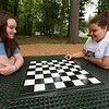 The new playground at Wallis Park in Lunenburg has some table with boards for chess or checkers but no pieces. That didn't stop Maya Beland, 12, and her cousin Sabrina Reed, 13, as they just used some sticks as pieces to play some checkers at the park on Thursday morning. SENTINEL & ENTERPRISE/JOHN LOVE