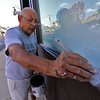 Freddy Basantes works on cleaning, sanding and then painting the windows at 37 Mechanic Street in Leominster on Wednesday afternoon. SENTINEL & ENTERPRISE/JOHN LOVE