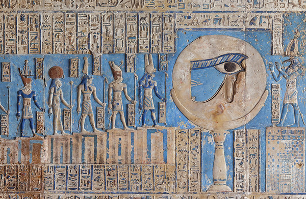 """07-calendar-egypt-dendera  Detail of the astronomical ceiling of the outer hypostyle hall in the Hathor Temple at Dendera. The ceiling has recently been cleaned in a careful way that removed hundreds of years of black soot, without harming the ancient paint underneath.  The image shows the moon on a pillar, decorated with the """"healed eye"""" of Horus. According to Egyptian mythology, Horus lost his eye in a battle with Seth, the murderer of his father Osiris. The eye was subsequently healed by Toth (who is portrayed at right). The destruction and healing of the eye was symbolically coupled to the waning and waxing of the moon. To the left of the moon are 14 stairs with gods, referring to the 14 days leading up to the full """"healed"""" moon. Photo Paul Smit."""