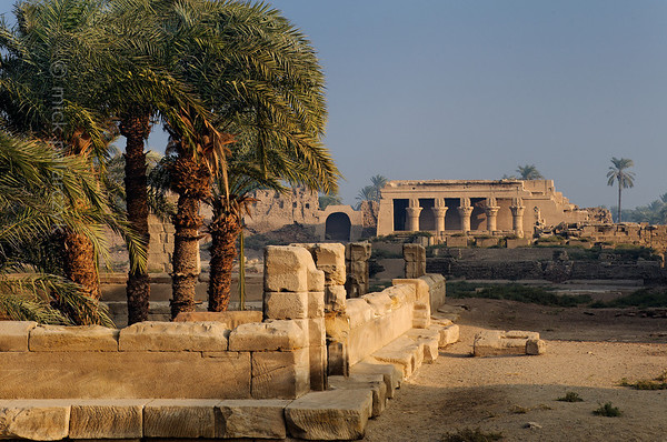 04-calendar-egypt-dendera  Temple grounds of the Hathor Temple at Dendera. On the foreground the low wall surrounding the sacred lake from the bottom of which palms grow. In the background the Roman birth house (mammisi). Photo Mick Palarczyk.