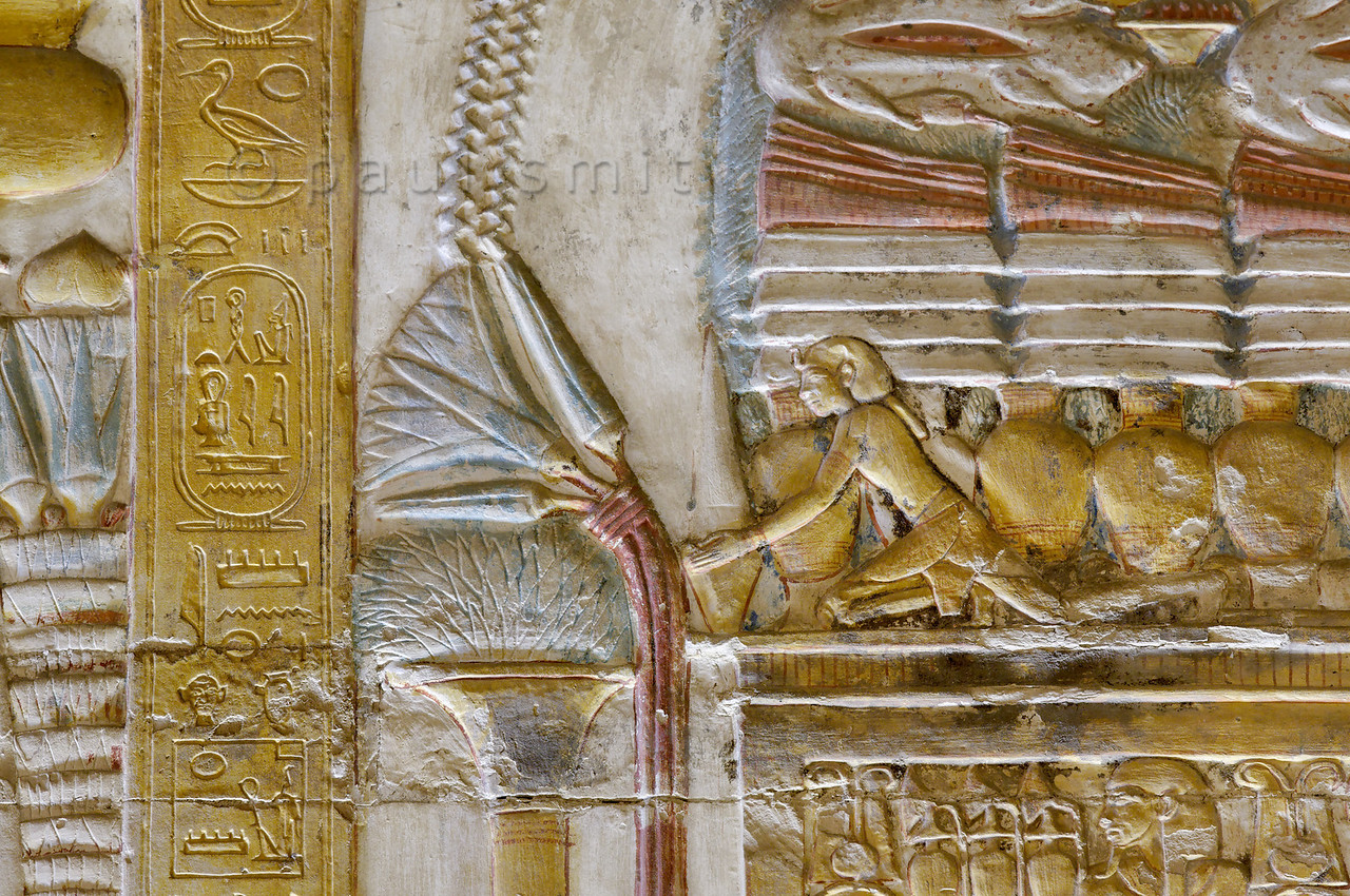 [EGYPT 29890] 'Offerings near Amun barque at Abydos.'  The Chapel of Amun in the Seti Temple in Abydos at one time probably housed a sacred portable barque of Amun. The sacred barque would have been used to carry a portable statue of the deity around the temple during festival processions, in imitation of the gods who were believed to cross the sky on their magical boats. The chapel, which is located directly west of the Second Hypostyle Hall, is decorated with detailed images of the sacred barque. Here we are looking at a relief detail on the north wall of the chapel. It shows several offerings which have been placed on and beside a table near the barque. Kneeling on the table is a statuette of a pharaoh that presents a vessel in which a conical bread has been placed.  The temple  was begun by Seti I and completed by his son Ramses II in the 13th century BC. Photo Paul Smit.