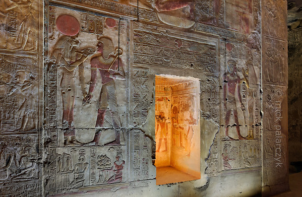"[EGYPT 29867] 'Seti, Sekhmet and Hathor at Abydos.'  	The west wall of the Second Hypostyle Hall of the Seti I Temple at Abydos is decorated with superb reliefs. Here we see a portion of wall that is located between the entrances of the Chapel of Ptah and the Chapel of Ra-Horakhty. On the left we see the lion-headed goddess Sekhmet clasping hands with Seti and holding the ""ankh"" sign before the mouth of the king. The sign is entwined in her ""menat"" necklace.  On the right Hathor gives the king the breath of life, in the form of an ""ankh"" sign (symbolizing life) flanked by two ""was"" sceptres (symbols for prosperity). The niche in the centre of the picture at one time probably held a statue of either Ptah or Ra-Horakhty. The decoration in the niche shows Seti offering incense to Ra-Horachti. The niche could also have been used to store sacred scrolls pertaining to the rites which were performed in the adjoining chapel. As the lower part of the niche is without decorations a stash of scrolls wouldn't have obscured the sacred images on its three walls. The lower register on each side of the niche is decorated with a series of Nile gods,  kneeling, hermaphrodite personifications of Egyptian nomes (districts). Each figure is basically male, with the breasts of a woman (symbolizing fecundity), and on its head there is an emblem which indicates the name of the nome. The figures carry food and jars of wine and water which they present to the gods. On the right we see the Lower Egyptian nomes number 15 and 13. On the left we see the Lower Egyptian nomes number 10 (with ox emblem) and 4.  The Seti Temple at Abydos was begun by Seti I and completed by his son Ramses II in the 13th century BC. Photo Mick Palarczyk."
