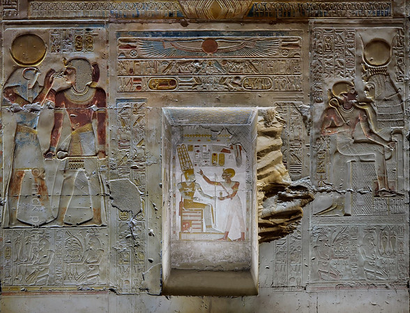 "[EGYPT 29865] 'Seti, Khonsu and Isis at Abydos.'  	The west wall of the Second Hypostyle Hall of the Seti I Temple at Abydos is decorated with superb reliefs. Here we see a portion of wall that is located between the entrances of the Chapel of Amun-Ra and the Chapel of Osiris. On the left we see Khonsu giving Seti the breath of life, in the form of an ""ankh"" sign (symbolizing life) flanked by two ""was"" sceptres (symbols for prosperity). Khonsu is depicted as a falcon-headed man wearing the crown of the full and the crescent moon. Khonsu was a protector and healer. On the right Isis caresses the king as a child.  She says to him: ""You are my son, you have come forth from me, I have nursed you, in order to be Ruler of the Two Lands."" Sitting in the lap of Isis, Seti has taken the role of Horus, Isis' child. The niche in the centre of the picture at one time probably held a statue of Amun-Ra. The niche is decorated with a scene in which Seti anoints the brow of Amun-Ra with ointment. The niche could also have been used to store sacred scrolls pertaining to the rites which were performed in the adjoining chapel. As the lower part of the niche is without decorations a stash of scrolls wouldn't have obscured the sacred images on its three walls. The lower register on each side of the niche is decorated with a series of Nile gods,  kneeling, hermaphrodite personifications of Egyptian nomes (districts). Each figure is basically male, with the breasts of a woman (symbolizing fecundity), and on its head there is an emblem which indicates the name of the nome. The figures carry food and jars of wine and water which they present to the gods. On the right we see the Upper Egyptian nomes number 6 (with crocodile emblem, region of Dendera) and 7 (with sistrum emblem, region of Hiw). On the left we see the Upper Egyptian nomes number 3 (region near Esna) and 5 (with two falcons emblem, region of Qift).  The Seti Temple at Abydos was begun by Seti I and completed by his son Ramses II in the 13th century BC. Photo Mick Palarczyk."
