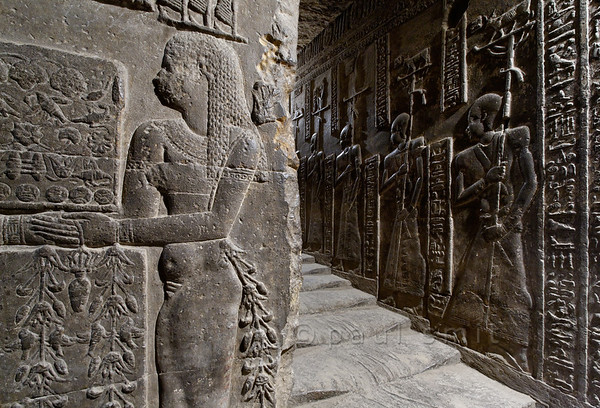 [EGYPT 29612] 'Stairs leading to temple roof at Dendera.'  	A relief in the temple of Dendera shows a fertility goddess (left) who is carrying a tray with breads and flowers down the western stairs of the temple. She is part of a procession which is accompanying a shrine (not in this picture) containing a statue of the soul of Hathor. On the temple roof the statue has been revitalized by the sun rays of the first day of the Egyptian year and is afterwards returned to a underground crypt where it is kept for the rest of the year. The left-hand side (facing up) of the winding stairs shows the descending procession while the right-hand side shows the same cortège climbing the stairs. Four standard bearing priests which are part of the ascending procession can be seen on the right side of the picture. This part of the temple dates from the first century AD. Photo Paul Smit.