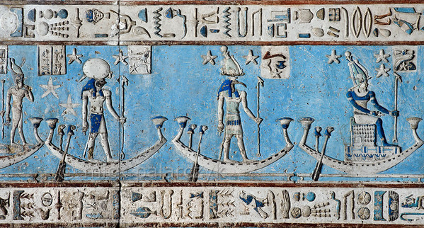 [EGYPT 29537] 'Decanal stars on boats in Hathor Temple at Dendera.'  Starry gods are sailing on boats across the firmament on the astronomical ceiling in the outer hypostyle hall of the Hathor Temple at Dendera. The ceiling consists of seven separate strips but here we are looking at a detail of the lower register of the EASTERNMOST STRIP. The seated human-headed god and the standing ibis-headed and falcon-headed gods are the decanal stars 33, 34 and 35. In fact, the lower register of the easternmost strip is entirely filled with figures who are standing or sitting in boats. These are the decans, 36 stars or star groups near the ecliptic  whose rise or transit could be used to tell the time during the night. Eventually they were also used by astronomers as place-markers in the sky to divide up the Ecliptic in equal portions. Decans first appear during the Middle Kingdom on the inside of coffin lids, providing the deceased with his own private start clock. Unfortunately, during the subsequent centuries many different lists of decanal stars were developed and very few of these stars can be identified on a modern star map. The decans in this register were listed by Neugebauer and Parker as stars 18 till 35 of the Tanis decan family. Stars 1 till 17 and 36 can be found on the westernmost ceiling strip. For an overview of the ceiling strip of which a detail is portrayed in this photo, see picture 29526. This part of the Dendera Temple was built during the Roman period (first century AD). Photo Mick Palarczyk.
