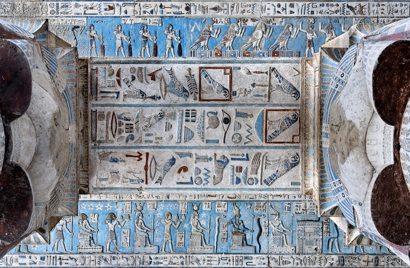 [EGYPT 29540] 'Architrave of astronomical ceiling in Hathor Temple at Dendera.'  An architrave supporting the astronomical ceiling in the outer hypostyle hall of the Hathor Temple at Dendera is decorated with superbly crafted hieroglyphs. The falcon within a square is the hieroglyphic sign for the patron goddess of the temple: Hathor. The astronomical ceiling consists in total of seven separate strips which are supported by six rows of columns with architraves (for an overview see pictures 29525 and 29539). The architrave in this picture is located between the first and second strip east from the central ceiling strip. At the bottom of the picture we see, against a bright blue background, starry deities from the upper register of the second strip east from central (for a detail see photo 29546). The top of the picture shows the lower register of the first strip east from central (for a detail see photo 29558). This part of the Dendera Temple was built during the Roman period (first century AD). Photo Paul Smit.