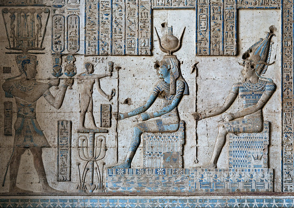 """[EGYPT 29602] 'Nero, Isis and Osiris in Dendera.'  A relief in the Hathor Temple at Dendera shows Isis (with sundisk) and Osiris sitting on thrones. The latter is actually described here as """"Osiris Unefer"""", the last part of the name (""""He who is always good"""") being presented within a cartouche. On the left Roman Emperor (and Pharaoh) Nero is presenting two sistrums, ritual musical instruments decorated with the head of Hathor. Before him stands the child god Ihy, son of Hathor and Horus. The relief is located on the (interior) eastern wall of the outer hypostyle hall of the Dendera temple and dates from the first century AD. Photo Paul Smit."""