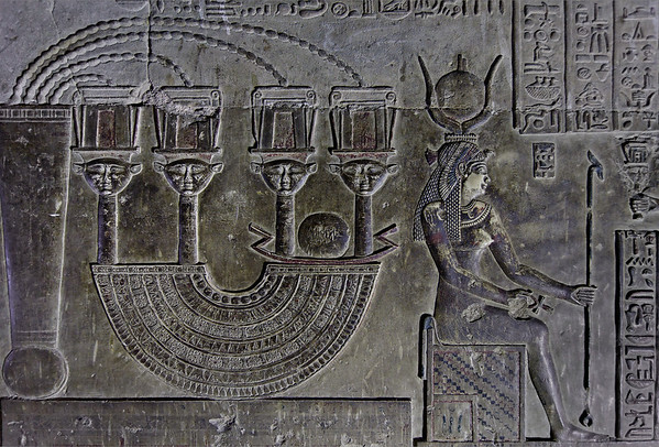 """[EGYPT 29608] 'Menat necklace in Dendera.'  The crypt below the southern wall of the Hathor Temple at Dendera was used for the safe keeping of several sacred objects and statues used in the rites of Hathor. On the walls of the crypt these objects are depicted in reliefs and described in some detail. Here we see such an object: a Menat necklace, which, when held in the hand and shaken, produced a rustling sound that was thought to please the goddess Hathor. The object consisted of a counterweight, which, when worn, was meant to be located at the back of the neck and which was connected by beaded strings to four sistrums and the actual semicircular necklace. The sistrums were musical instruments in their own right and each was decorated with the face of Hathor. The faces symbolized the four cardinal points of the universe and stress the universal character of the sky goddess Hathor, who was also called """"Lady with the four Faces"""". Between two of the heavenly sistrums the solar bark glides through the sky. On the right we see Isis seated on a throne. This part of the Dendera Temple was built during the later Ptolemaic period (first century BC). Photo Mick Palarczyk."""