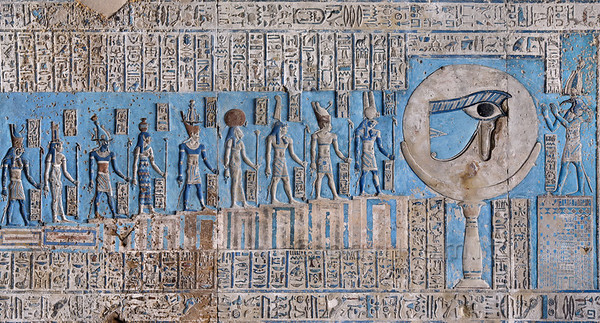 "[EGYPT 29566] 'The waxing moon and the Eye of Horus at Dendera.'  	This forceful image of the moon on a pillar, decorated with the ""healed eye"" of Horus, can be found on the astronomical ceiling of the outer hypostyle hall in the Hathor Temple at Dendera. The astronomical ceiling consists of seven separate strips but here we are looking at a detail of the FIRST STRIP WEST from centre. The deities in this picture form part of a panel that deals with the waxing moon and which is located at the middle of the strip. According to Egyptian mythology Horus lost his eye during a battle with Seth (the murderer of his father Osiris) and the eye (called 'Wadjet') was subsequently healed by Thoth, who is portrayed at the right-hand side of the picture. The destruction and healing of the eye was symbolically coupled by the ancient Egyptians to the waning and waxing of the moon. To the left of the moon are 14 stairs (of which only 9 are visible in this picture) with gods who refer to the 14 days leading up to the full ""healed"" moon. From right to left they are Min (1), Atum (2), Shu (3), Tefnut (4), Geb (5), Nut (6), Osiris (7), Isis (8 ) and Horus (9). The other five are outside the frame of this picture but can be seen in photo 29565. For an overview of the entire ceiling strip see picture 29561. This part of the Dendera Temple was built during the Roman period (first century AD). Photo Paul Smit."
