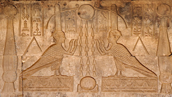 "[EGYPT 29618] 'Souls of Osiris at Dendera.'  	Two images of the soul (ba) of Osiris in the form of a human headed bird decorate the court of the eastern Osiris chapels on the roof of the Hathor Temple at Dendera. The heads are topped by absurdly big ""perfume cones"". The birds are placed on either side of three sun rays which connect a sun up in the sky and another one which is sitting on the horizon. This part of the Dendera Temple was built during the later Ptolemaic period (first century BC). Photo Mick Palarczyk."