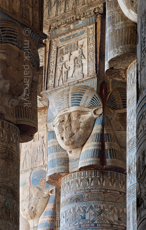 """[EGYPT 29516] 'Hathor headed columns in Dendera.'  The columns in the outer hypostyle hall (or pronaos) of the Hathor Temple at Dendera are crowned by four-sided capitals carved with the face of the cow-eared goddess. The faces symbolize the four cardinal points of the universe and stress the universal character of the sky goddess Hathor, who was also called """"Lady with the four Faces"""". The square structure that is placed on top of the actual face is a sistrum, a ritual musical instrument that produced a rustling sound that was thought to please Hathor. The tiny plates which would make the sound are not visible here, however. Instead a scene is depicted with a seated Hathor suckling the child-god Harsomptus. This part of the Dendera Temple was built during the Roman period (first century AD). Photo Mick Palarczyk."""