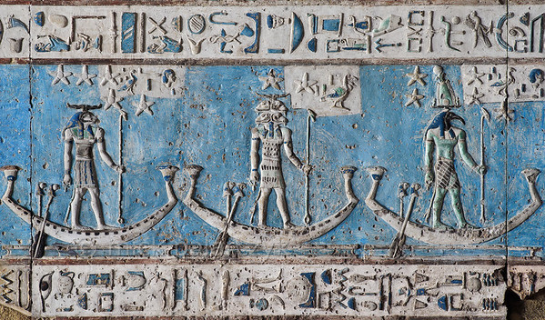 [EGYPT 29538] 'Decanal stars on boats in Hathor Temple at Dendera.'  Starry gods are sailing on boats across the firmament on the astronomical ceiling in the outer hypostyle hall of the Hathor Temple at Dendera. The ceiling consists of seven separate strips but here we are looking at a detail of the lower register of the EASTERNMOST STRIP. The ram-headed god, the god with four ram heads and the ibis-headed god are the decanal stars 25, 24 and 23. In fact, the lower register of the easternmost strip is entirely filled with figures who are standing or sitting in boats. These are the decans, 36 stars or star groups near the ecliptic  whose rise or transit could be used to tell the time during the night. Eventually they were also used by astronomers as place-markers in the sky to divide up the Ecliptic in equal portions. Decans first appear during the Middle Kingdom on the inside of coffin lids, providing the deceased with his own private start clock. Unfortunately, during the subsequent centuries many different lists of decanal stars were developed and very few of these stars can be identified on a modern star map. The decans in this register were listed by Neugebauer and Parker as stars 18 till 35 of the Tanis decan family. Stars 1 till 17 and 36 can be found on the westernmost ceiling strip. For an overview of the ceiling strip of which a detail is portrayed in this photo, see picture 29526. This part of the Dendera Temple was built during the Roman period (first century AD). Photo Mick Palarczyk.
