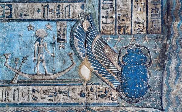 [EGYPT 29592] 'Birth of the sun in Hathor Temple at Dendera.'  	The rising sun is born from the lap of sky goddess Nut in the form a winged scarab beetle on the astronomical ceiling in the outer hypostyle hall of the Hathor Temple at Dendera. The ceiling consists of seven separate strips but here we are looking at the northern end of the lower register of the WESTERNMOST STRIP.  The entire strip is enveloped by the outstretched body of the sky goddess Nut but here only her thigh (on the right) and a narrow section of her belly (at the lower edge of the picture) are visible. The wave pattern on Nut's dress symbolizes the cosmic river on which the sun traveled during the night.  On the left the standing god in a boat is a personification of decanal star number 36. In fact, the lower register of the westernmost strip is entirely filled with figures who are standing or sitting in boats. These are the decans, 36 stars or star groups near the ecliptic  whose rise or transit could be used to tell the time during the night.  Eventually they were also used by astronomers as place-markers in the sky to divide up the Ecliptic in equal portions. Decans first appear during the Middle Kingdom on the inside of coffin lids, providing the deceased with his own private start clock. Unfortunately, during the subsequent centuries many different lists of decanal stars were developed and very few of these stars can be identified on a modern star map. The decans in this register were listed by Neugebauer and Parker as stars 1 till 17 and 36 of the Tanis decan family. Stars 18 till 35 can be found on the easternmost ceiling strip (see picture 29526). This part of the Dendera Temple was built during the Roman period (first century AD). Photo Mick Palarczyk.