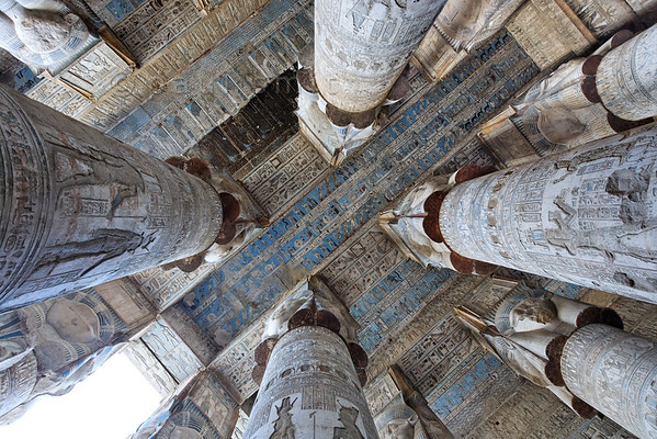 [EGYPT 29552] 'Astronomical ceiling in Hathor Temple at Dendera.'  Looking up in the outer hypostyle hall of the Hathor Temple at Dendera gives you a dazzling view of the astronomical ceiling. It is a mysterious world inhabited by star gods and zodiac  signs but also by weirder creatures such as snakes on tall legs and birds with human heads.  The astronomical ceiling consists in total of seven separate strips, which are conspicuous by their bright blue colour. Here we see, in the upper left corner, the central strip, where the layer of black soot, that until recently covered the entire ceiling, has only been partly cleaned away. The rest of the picture shows the three ceiling strips which are located east from the central one. The FIRST STRIP EAST from centre we see in its entirety in this photo. It is dedicated to the daily course of the sun (and so mirrors the subject of the first strip west from centre which deals with the moon and its phases). It consists of three registers separated by bands of text. In the middle register the sun is traveling across the sky during the twelve hours of the day. For every hour the sun is depicted in its bark, with a goddess, crowned by a sun disk, standing in adoration before its bow. The voyage starts at the left side where the sun god, just after its birth in the morning, is portrayed as a child during the first hour of the day. The lower and upper registers of this ceiling strip are inhabited by deities who protect the sun during its voyage. For an overview of the entire astronomical ceiling see picture 29525. This part of the Dendera Temple was built during the Roman period (first century AD). Photo Paul Smit.