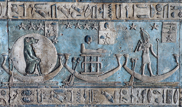 [EGYPT 29591] 'Decanal stars on boats in Hathor Temple at Dendera.'  Starry creatures are sailing in boats across the firmament on the astronomical ceiling in the outer hypostyle hall of the Hathor Temple at Dendera. The ceiling consists of seven separate strips but here we are looking at a detail of the lower register of the WESTERNMOST STRIP. The squatting baboon, the figure group and the standing god are the decanal stars no. 12, 11 and 10. The boat of no. 11 is transporting the three hieroglyphic signs which make up the name of this heavenly body: a head, an arm and a stand for three water jugs. In fact, the lower register of the westernmost strip is entirely filled with figures who are standing or sitting in boats. These are the decans, 36 stars or star groups near the ecliptic  whose rise or transit could be used to tell the time during the night.  Eventually they were also used by astronomers as place-markers in the sky to divide up the Ecliptic in equal portions. Decans first appear during the Middle Kingdom on the inside of coffin lids, providing the deceased with his own private start clock. Unfortunately, during the subsequent centuries many different lists of decanal stars were developed and very few of these stars can be identified on a modern star map. The decans in this register were listed by Neugebauer and Parker as stars 1 till 17 and 36 of the Tanis decan family. Stars 18 till 35 can be found on the easternmost ceiling strip (see picture 29526). This part of the Dendera Temple was built during the Roman period (first century AD). Photo Mick Palarczyk.