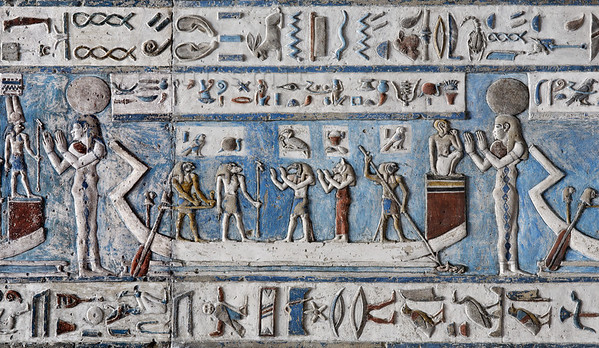 "[EGYPT 29555] 'The sun in its bark at Dendera.'  	Worshipped by an ibis-headed Thoth and a cat-headed Bastet, Ra (with dog head) is traveling across the sky in his solar bark on the astronomical ceiling in the outer hypostyle hall of the Hathor Temple at Dendera. The ceiling consists of seven separate strips but here we are looking at a detail of the middle register of the FIRST STRIP EAST from centre. The whole of this register deals with the daily voyage of the sun god and for everyone of the twelve hours the sun is depicted in its bark, with a goddess, crowned by a sun disk, standing in adoration before its bow. The text band below and above this register amongst others mentions that Ra "" travels with a joyful heart"", that he is ""King of Time"" and the ""he guides the heart to fulfill itself"". This picture shows Ra's voyage during the eight hour of the day.	 Near the stern of the boat a pilot is manipulating the two steering oars. Near the bow a falcon-headed Horus is spearing the water snake Apophis, the archenemy of Ra.  For an overview of this ceiling strip see picture 29552. This part of the Dendera Temple was built during the Roman period (first century AD). Photo Paul Smit."