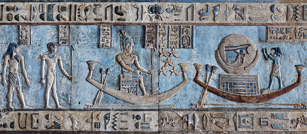 [EGYPT 29581] 'Osiris and the moon on astronomical ceiling at Dendera.'  	Boats carrying Osiris and the moon sail across the sky on the astronomical ceiling in the outer hypostyle hall of the Hathor Temple at Dendera. The ceiling consists of seven separate strips but here we are looking at a detail of the lower register of the SECOND STRIP WEST from centre. Worshipped by Thoth, the boat on the right transports a full moon which is decorated with the Wadjet eye. According to Egyptian mythology Horus lost his eye during a battle with Seth (the murderer of his father Osiris) and the eye (called 'Wadjet') was subsequently healed by Thoth. The destruction and healing of the eye was symbolically coupled by the ancient Egyptians to the waning and waxing of the moon. The boat in the middle of the picture carries an enthroned Osiris personifying the full moon. See picture 29572 for a zoomed out view of this ceiling strip. This part of the Dendera Temple was built during the Roman period (first century AD). Photo Paul Smit.