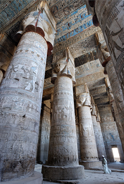 """[EGYPT 29514] 'Outer hypostyle hall of Hathor Temple at Dendera.'  The columns in the outer hypostyle hall (or pronaos) of the Hathor Temple at Dendera are crowned by four-sided capitals carved with the face of the cow-eared goddess. The faces symbolize the four cardinal points of the universe and stress the universal character of the sky goddess Hathor, who was also called """"Lady with the four Faces"""". The square structure that is placed on top of the actual face is a sistrum, a ritual musical instrument that produced a rustling sound that was thought to please Hathor. The ceiling of the hall has recently been cleaned of soot and dust and is decorated with a complex set of astronomical figures, constellations, planets and a zodiac. The shafts of the columns bear the image of a pharaoh (recognizable by his blue crown) who can be identified by his cartouches as the Roman emperor Claudius. This part of the Dendera Temple was built during the Roman period (first century AD). Photo Mick Palarczyk."""