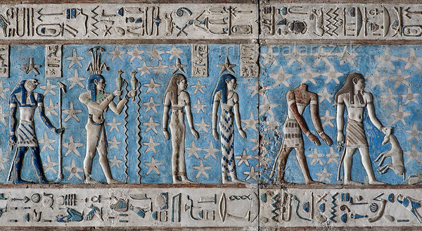 [EGYPT 29534] 'Zodiac sign Aquarius at Dendera.'  Wearing a papyrus crown and pouring water from two vessels, the Nile-god Hapi personifies the zodiac  sign Aquarius on the astronomical ceiling in the outer hypostyle hall of the Hathor Temple at Dendera. The ceiling consists of seven separate strips but here we are looking at a detail of the upper register of the EASTERNMOST STRIP. There are six zodiac signs depicted in the entire easternmost strip and the other six can be found on the westernmost ceiling strip of the hall. These signs are of Babylonic-Greek origin and are not found in Egypt before it was conquered by Alexander the Great in 332 BC, but of course Hapy is present in Egyptian iconography much earlier. The falcon-headed god on the left is the planet Mars (called 'Horus-the-Red'). The standing women with stars above their heads are the goddesses of the third and second hour of the night. The headless human body personifies a star or constellation north of the Ecliptic. Also north of the Ecliptic is the constellation made up of an human-headed-god holding an oryx by the horns. The astronomical location of both heavenly bodies is known from the famous round zodiac of Dendera which is kept in the Louvre. For an overview of this ceiling strip see picture 29526. This part of the Dendera Temple was built during the Roman period (first century AD). Photo Mick Palarczyk.
