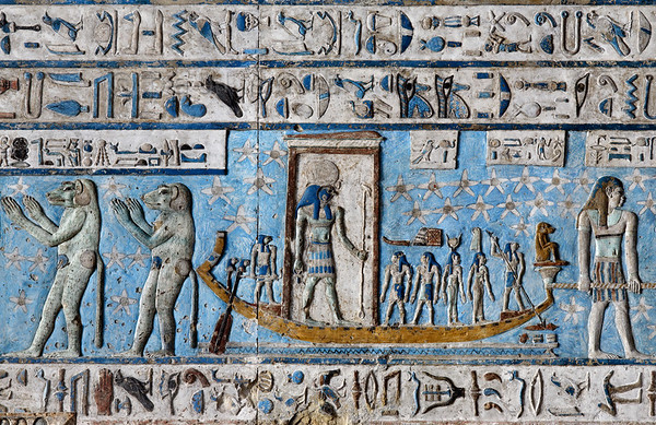 "[EGYPT 29544] 'Sun god sailing across the sky at Dendera.'  	The sun god Ra is sailing across the sky on the astronomical ceiling in the outer hypostyle hall of the Hathor Temple at Dendera. The ceiling consists of seven separate strips but here we are looking at a detail of the lower register of the SECOND STRIP EAST from centre. The sun, depicted in his falcon-headed form of Ra-Horakhty ('Ra who is Horus of the Horizons'), is standing in a shrine on his sun-bark. Behind him, the helmsman is manipulating the steering oars. Near the bow a falcon-headed god is spearing Apophis, the big snake that is the archenemy of Ra (only his hieroglyphic signs are shown here, lurking in the water.) The spear bearer is followed by Maat (the goddess of truth) , Isis and Sia (the personification of knowledge). The bark is pulled over the heavenly river by three men, only one of which is visible in this picture. A text placed above them designates them as ""Stars that accompany the sun in the southern sky.""	 On the left baboons worship another boat which transports the rising sun (not visible in this picture). The caption over their heads calls them the ""Souls of the East"". Baboons were observed by ancient Egyptians to screech at the rising sun, warming themselves in its rays, and this probably formed the inspiration for this favourite scene in Egyptian iconography. For an overview of this ceiling strip see picture 29539. This part of the Dendera Temple was built during the Roman period (first century AD). Photo Paul Smit."