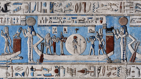 "[EGYPT 29554] 'The sun in its bark at Dendera.'  	Enveloped by the disc  of the sun, the sun god Ra is traveling across the sky in his solar bark on the astronomical ceiling in the outer hypostyle hall of the Hathor Temple at Dendera. The ceiling consists of seven separate strips but here we are looking at a detail of the middle register of the FIRST STRIP EAST from centre. The whole of this register deals with the daily voyage of the sun god and for everyone of the twelve hours the sun is depicted in its bark, with a goddess, crowned by a sun disk, standing in adoration before its bow. The text band below and above this register amongst others mentions that Ra "" travels with a joyful heart"", that he is ""King of Time"" and ""he guides the heart to fulfill itself"". This picture shows  Ra's voyage during the fifth hour of the day. On either side of the sun disc, Isis and Thoth are standing in adoration.	 Behind Isis is the cat-headed goddess Bastet. Near the stern of the boat a pilot is manipulating the two steering oars. Near the bow a falcon-headed god is spearing a turtle, symbol of the evil spirited god Seth.  At the left-hand edge of the picture we see a similar falcon-headed god, standing in the bow of the sun bark of the fourth hour. He is spearing a man who belongs to one of the traditional enemies of Egypt.  For an overview of this ceiling strip see picture 29552. This part of the Dendera Temple was built during the Roman period (first century AD). Photo Paul Smit."