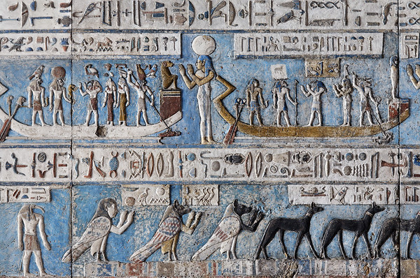 "[EGYPT 29556] 'The sun in its bark at Dendera.'  	Portrayed during the ninth and tenth hour of the day Ra is traveling across the sky in his solar bark on the astronomical ceiling in the outer hypostyle hall of the Hathor Temple at Dendera. The ceiling consists of seven separate strips but here we are looking at a detail of the middle and lower register of the FIRST STRIP EAST from centre. The whole of the middle register deals with the daily voyage of the sun god and for everyone of the twelve hours the sun is depicted in its bark, with a goddess, crowned by a sun disk, standing in adoration before its bow. The text band below and above this register amongst others mentions that Ra "" travels with a joyful heart"", that he is ""King of Time"" and ""he guides the heart to fulfill itself"". This picture shows Ra's voyage during the ninth and tenth hour of the day.  During the ninth hour (on the left) he has the head of a lion and is crowned by a sun disc. Before him stands Thoth in a worshipping position, followed by the cat-headed Bastet and a goddess who is crowned by a wadjet eye.  Near the stern of the boat a falcon-headed pilot is manipulating the two steering oars. Near the bow a falcon-headed Horus is spearing a man who belongs to one of the traditional enemies of Egypt. During the tenth hour (on the right) the sun god has the head of a ram. Before him stands Thoth in a worshipping position, followed by the goddess of truth, Maat. Near the bow a ram-headed god is spearing a donkey who is also kept on a chain. The donkey is a symbolical animal for the evil spirited Seth. The lower register of this ceiling strip is inhabited by deities who protect or help the sun during its voyage. The black jackals on the right  are called ""Sailors of the sun-bark"". Next to them are three 'ba' souls in the form of a human-headed and jackal-headed birds with human arms making a worshipping gesture. They are called ""Souls of the first day of the month"". For an overview of this ceiling strip see picture 29552. This part of the Dendera Temple was built during the Roman period (first century AD). Photo Paul Smit."