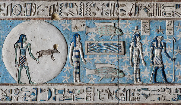 "[EGYPT 29533] 'Zodiac sign Pisces at Dendera.'  	A fish on either side of a pond makes up the zodiac  sign Pisces on the astronomical ceiling in the outer hypostyle hall of the Hathor Temple at Dendera. The ceiling consists of seven separate strips but here we are looking at a detail of the upper register of the EASTERNMOST STRIP. There are six zodiac signs depicted in the entire easternmost strip and the other six can be found on the westernmost ceiling strip of the hall. These signs are of Babylonic-Greek origin and are not found in Egypt before it was conquered by Alexander the Great in 332 BC. The standing women to the left and the right of the fish are the goddesses of the 5th and 4th hour of the night. The disk with a god holding a small pig by a hind foot is interpreted by some scholars as the sun being eclipsed, but this can't be proven.	 The falcon-headed god on the right is the planet Mars (called 'Horus-the-Red). Other Egyptian astronomical texts mention that the god ""travels backwards', which is undoubtedly an allusion to the retrograde movement of Mars. Of course other planets display this movement also, but maybe the Egyptians found it particularly striking in Mars. For an overview of this ceiling strip see picture 29526. This part of the Dendera Temple was built during the Roman period (first century AD). Photo Mick Palarczyk."