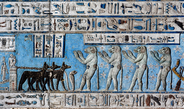 """[EGYPT 29543] 'Baboons worshipping the rising sun at Dendera.'  Four baboons are welcoming and worshipping the rising sun on the astronomical ceiling in the outer hypostyle hall of the Hathor Temple at Dendera. The ceiling consists of seven separate strips but here we are looking at a detail of the lower register of the SECOND STRIP EAST from centre. Near the left edge of the picture we can just discern the bow of a boat which carries the image of a seated child. This boat carries the rising sun (which is outside the frame of the picture) and is pulled into the eastern sky by three black jackals (called """"The Justified""""). Four standing baboons await the sun in a worshipping position. The caption over their heads calls them the """"Souls of the East"""". Baboons were observed by ancient Egyptians to screech at the rising sun, warming themselves in its rays, and this probably formed the inspiration for this favourite scene in Egyptian iconography. For an overview of this ceiling strip see picture 29539. This part of the Dendera Temple was built during the Roman period (first century AD). Photo Paul Smit."""