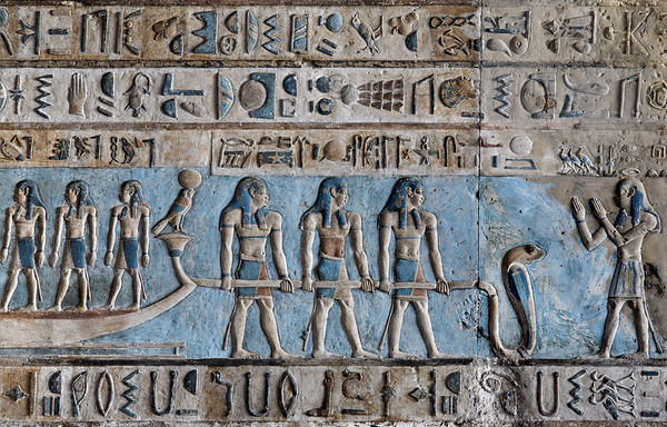 """[EGYPT 29582] 'Pulling the sun bark at Dendera.'  Three gods are pulling the sun bark across the sky on the astronomical ceiling in the outer hypostyle hall of the Hathor Temple at Dendera. The ceiling consists of seven separate strips but here we are looking at a detail of the lower register of the SECOND STRIP WEST from centre. A caption above the three men mentions that """"they are the stars who accompany the sun in the northern sky."""" That fits with the main passenger of the boat: Atum, personification of the evening sun (he is just outside the frame of this photo, but see picture 29572 for zoomed out view). The worshipping man on the right is one of three Souls of the West who welcome the solar bark. This part of the Dendera Temple was built during the Roman period (first century AD). Photo Paul Smit."""