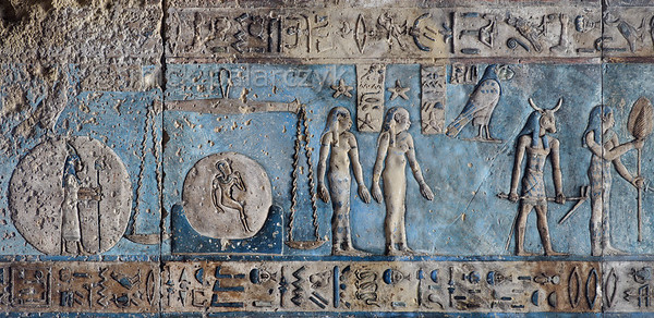 "[EGYPT 29589] 'Libra and Virgo on astronomical ceiling at Dendera.'  	Scales and a woman holding an ear of corn portray the zodiac  signs Libra and Virgo on the astronomical ceiling in the outer hypostyle hall of the Hathor Temple at Dendera. The ceiling consists of seven separate strips but here we are looking at a detail of the upper register of the WESTERNMOST STRIP. The scales of Libra are positioned over the hieroglyphic sign for 'horizon' (with a child depicted within the circle of the sun), perhaps referring to the horizontality of the scales' arm. There are six zodiac signs depicted in the entire westernmost strip (see picture 29585 till 29590) and the other six can be found on the easternmost ceiling strip of the hall (see picture 29526). These signs are of Babylonic-Greek origin and are not found in Egypt before it was conquered by Alexander the Great in 332 BC. On the left, the human-headed goddess inside a disk represents a star or constellation which is only known from this astronomical ceiling. The hardly visible falcon above it is thought to represent the planet Venus. In the centre of the picture the two standing women with stars above theirs heads are the goddesses of the eight and ninth hour of the night. The frog-headed falcon (identified by a caption as 'Sebek') is a personification of the planet Mercury. In a text dating from the New Kingdom Mercury was described as ""Seth in the evening twilight and a god in the morning twilight."" Proof that by that time Mercury was known as both evening and morning star. 	The bull-headed god holding a hoe has been identified by some scholars as the constellation of Boötes. However, Boötes lies north of the ecliptic and the round zodiac of Dendera (which is kept in the Louvre) places this same bull-headed god south of it, so the identification is not certain. This part of the Dendera Temple was built during the Roman period (first century AD). Photo Mick Palarczyk."