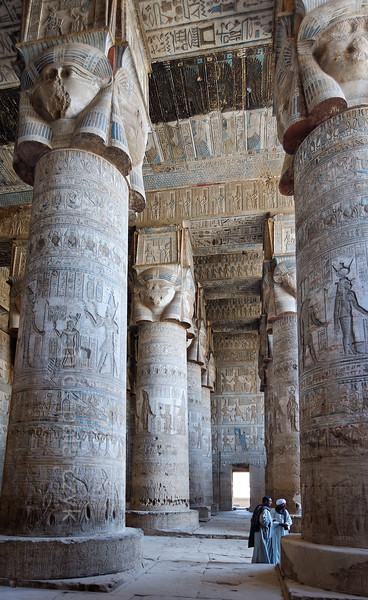 "[EGYPT 29513] 'Outer hypostyle hall of Hathor Temple at Dendera.'  	The columns in the outer hypostyle hall (or pronaos) of the Hathor Temple at Dendera are crowned by four-sided capitals carved with the face of the cow-eared goddess. The faces symbolize the four cardinal points of the universe and stress the universal character of the sky goddess Hathor, who was also called ""Lady with the four Faces"". The square structure that is placed on top of the actual face is a sistrum, a ritual musical instrument that produced a rustling sound that was thought to please Hathor. The ceiling of the hall has recently been cleaned of soot and dust. One strip has been left uncleaned however and this is visible as a black zone in the upper half of the picture. This part of the Dendera Temple was built during the Roman period (first century AD). Photo Mick Palarczyk."