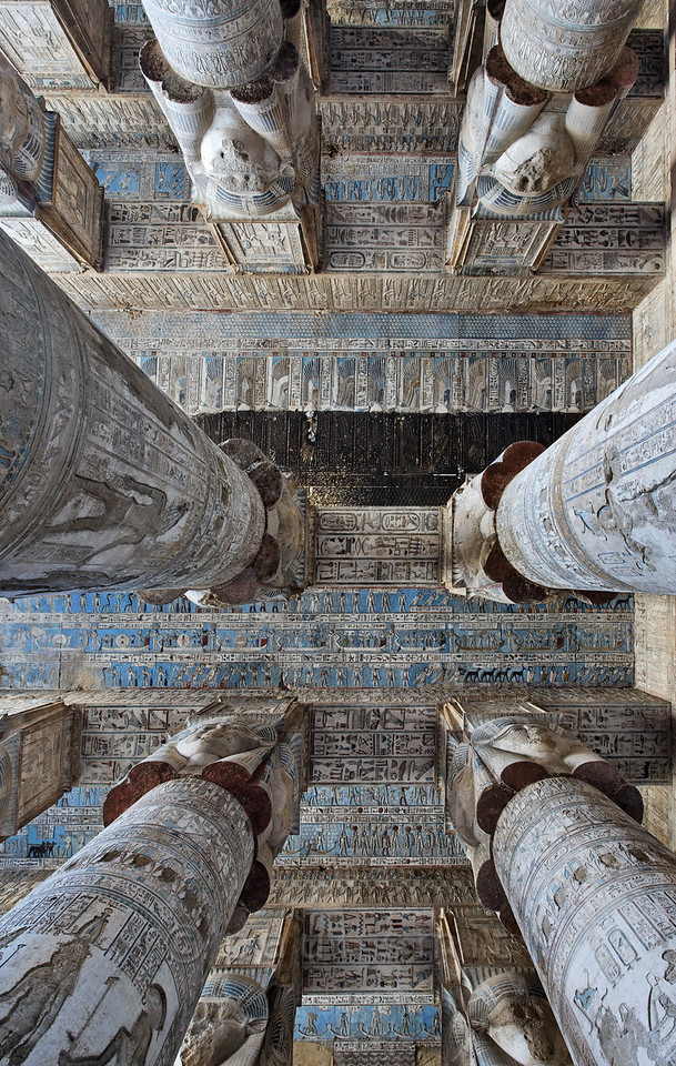 [EGYPT 29553] 'Astronomical ceiling in Hathor Temple at Dendera.'  Looking up in the outer hypostyle hall of the Hathor Temple at Dendera gives you a dazzling view of the astronomical ceiling. It is a mysterious world inhabited by star gods and zodiac  signs but also by weirder creatures such as snakes on tall legs and birds with human heads.  The astronomical ceiling consists in total of seven separate strips, which are conspicuous by their bright blue colour. Here we see, just above the middle of the picture, the central ceiling strip, where the layer of black soot, that until recently covered the entire ceiling, has only been partly cleaned away. Above that we see part of the first and second strip west from centre. The lower half of the picture is filled with parts of the three strips east from centre. The first strip east from centre we see most clearly in this picture, as it is not obscured by columns. It consist of three registers. The middle register  deals with the daily voyage of the sun god across the sky. For every one of the twelve hours the sun is depicted in its bark, with a goddess, crowned by a sun disk, standing in adoration before its bow. The lower and upper registers of this ceiling strip are inhabited by deities who protect the sun during its voyage, which progresses from left to right. For a more complete overview of this ceiling strip see picture 29552. For an overview of the entire astronomical ceiling see picture 29525. This part of the Dendera Temple was built during the Roman period (first century AD). Photo Paul Smit.
