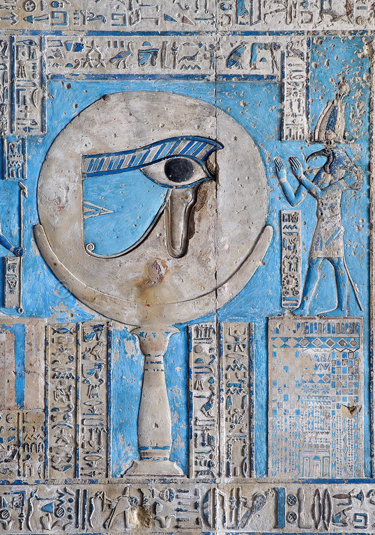 "[EGYPT 29568] 'The waxing moon and the Eye of Horus at Dendera.'  	This forceful image of the moon on a pillar, decorated with the ""healed eye"" of Horus, can be found on the astronomical ceiling of the outer hypostyle hall in the Hathor Temple at Dendera. The astronomical ceiling consists of seven separate strips but here we are looking at a detail of the FIRST STRIP WEST from centre. The moon eye is part of a panel that deals with the waxing moon and which is located at the middle of the strip. According to Egyptian mythology Horus lost his eye during a battle with Seth (the murderer of his father Osiris) and the eye (called 'Wadjet') was subsequently healed by Thoth, who is portrayed at the right-hand side of the picture.	 The destruction and healing of the eye was symbolically coupled by the ancient Egyptians to the waning and waxing of the moon. To the left of the moon are 14 stairs (outside the frame of the picture) with gods who refer to the 14 days leading up to the full ""healed"" moon. The entire scene can be seen in photo 29565. For an overview of the entire ceiling strip see picture 29561. This part of the Dendera Temple was built during the Roman period (first century AD). Photo Mick Palarczyk."
