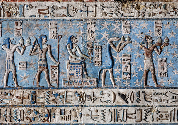 [EGYPT 29547] 'Stars, gods and minerals at Dendera.'  	Lined up against a starry background these colourful deities inhabit the astronomical ceiling in the outer hypostyle hall of the Hathor Temple at Dendera. The ceiling consists of seven separate strips but here we are looking at a detail of the upper register of the SECOND STRIP EAST from centre. The figures in this picture represent decans. Decans were essentially 36 stars or star groups near the ecliptic  whose rise or transit could be used to tell the time during the night. Eventually they were also used by astronomers as place-markers in the sky to divide up the Ecliptic in equal portions. Decans first appear during the Middle Kingdom on the inside of coffin lids, providing the deceased with his own private start clock. Unfortunately, during the subsequent centuries many different lists of decanal stars were developed and very few of these stars can be identified on a modern star map.	 The decans in this register were listed by Neugebauer and Parker as belonging to the Seti I B decan family. A peculiarity of these decans is that each is associated with a certain mineral, metal or type of wood. It is mentioned in a little caption near the lower part of each figure. Thus the serpent-headed god on the left is decan no. 35 and is associated with gold. The human-headed god, no. 34a, is coupled with quartz and gold. The seated lion-headed goddess (no. 34) presides over glass and gold. The long legged blue snake (no.33) watches over quartz and gold, while the lion-headed figure on the right (no. 32) is associated with granite and gold. For an overview of this ceiling strip see picture 29539. This part of the Dendera Temple was built during the Roman period (first century AD). Photo Paul Smit.
