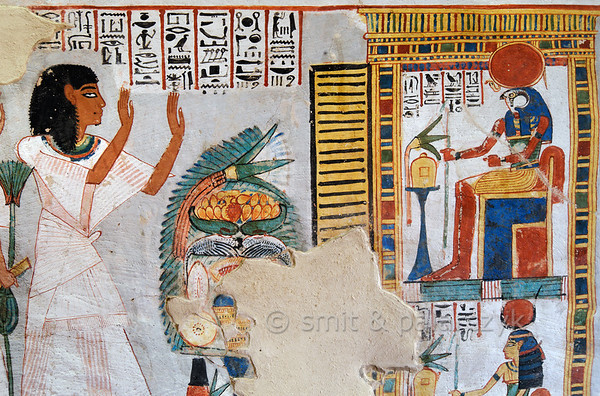 "[EGYPT 29384] 'Offerings for Ra-Horakhty and Hathor in Roy's tomb at Luxor.'  	A mural detail in the tomb of Roy shows a man presenting a table with offerings to two gods in a shrine. The gods accepting the offerings are Ra-Horakhty (top) and Hathor (below). Their wigs are dark blue to imitate the lapis-lazzuli, of which the hair of gods is supposed to be made. Roy was an 18th dynasty royal scribe during the reign of Horemheb. His tomb (TT 255) can be found in the Necropolis of Dra Abu el-Naga on the Westbank at Luxor. It is one of the socalled ""Tombs of the Nobles"". Photo Mick Palarczyk and Paul Smit."