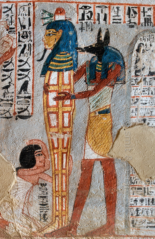 """[EGYPT 29379] 'Standing mummy in Roy's tomb at Luxor.'  A mural detail in the tomb of Roy shows his mummy being placed upright by a priest with an Anubis mask near the entrance of his tomb. Behind the priest stands a stela which addresses Osiris. The base of the mummy is embraced by Roy's wife who makes a gesture of mourning. Roy was an 18th dynasty royal scribe during the reign of Horemheb. His tomb (TT 255) can be found in the Necropolis of Dra Abu el-Naga on the Westbank at Luxor. It is one of the socalled """"Tombs of the Nobles"""". Photo Mick Palarczyk and Paul Smit."""