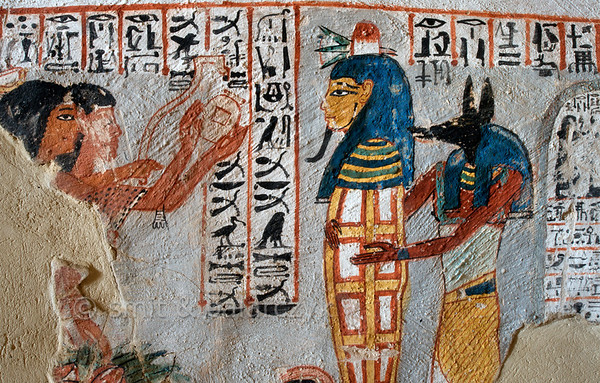 """[EGYPT 29380] 'Opening of the Mouth Ritual in Roy's tomb at Luxor.'  A mural detail in the tomb of Roy shows the """"Opening of the Mouth"""" ritual being performed on Roy's mummy by the Sem priest on the far left. With an adze (and other instruments not presented) he is going to touch the different openings of the face so that the deceased will be able to breath, eat and speak in the afterlife. A man behind the Sem priest holds a vessel in two hands from which he will pour a libation. The mummy is kept upright by another priest who wears an Anubis mask. On the far right we see part of a stela which has been erected near the entrance of the grave. Roy was an 18th dynasty royal scribe during the reign of Horemheb. His tomb (TT 255) can be found in the Necropolis of Dra Abu el-Naga on the Westbank at Luxor. It is one of the socalled """"Tombs of the Nobles"""". Photo Mick Palarczyk and Paul Smit."""